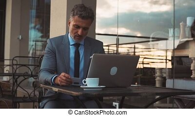 Mature businessman with laptop in a hotel lobby.