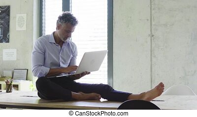 Mature businessman with laptop in creative office.
