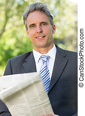 Mature businessman with newspaper in park