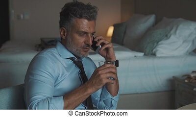 Mature businessman with smartphone in a hotel room. Handsome...