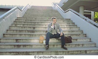 Mature businessman with smartphone in the city, making phone call