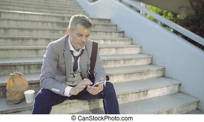 Mature businessman with smartphone in the city, reading...