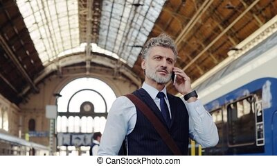 Mature businessman with smartphone on a train station. -...