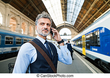 Mature businessman with smartphone on a train station.