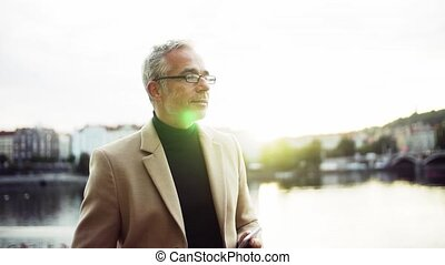 Mature businessman with smartphone standing by river at...