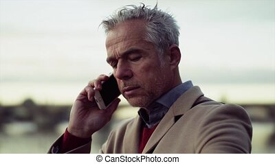 Mature businessman with smartphone standing by river in...