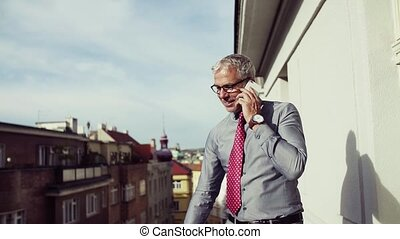 Mature businessman with smartphone standing on a terrace in...