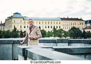 Mature businessman with suitcase standing on a bridge in Prague city.