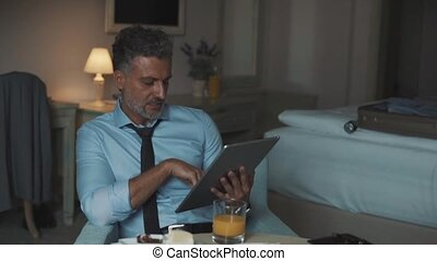 Mature businessman with tablet in a hotel room. - Mature,...