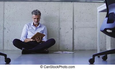 Mature businessman with tablet in creative office.