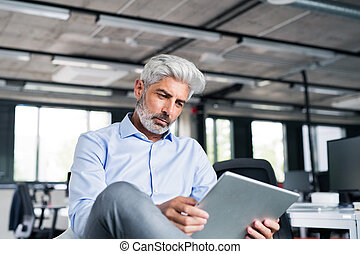 Mature businessman with tablet in the office.