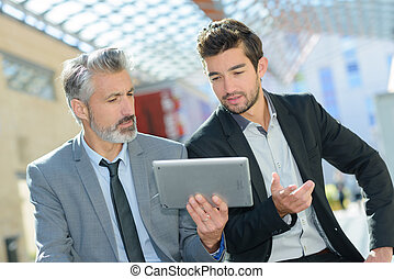 mature businessman with tablet with younger colleague