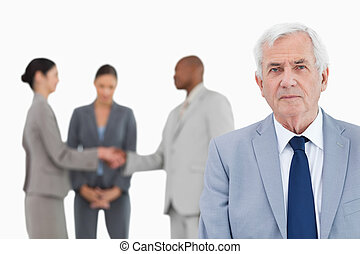 Mature businessman with trading partners behind him