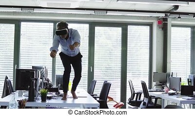 Mature businessman with VR goggles in the office. Man...