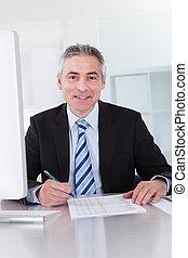 Mature Businessman Working At Desk