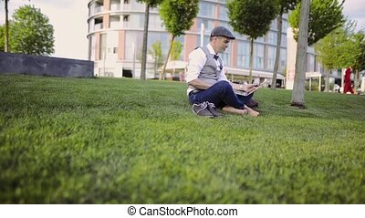 Mature businessman working on laptop in city park. -...