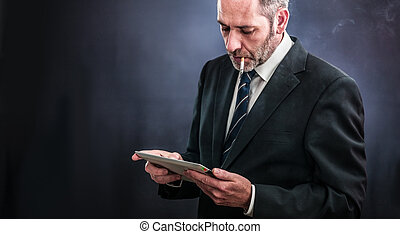 Mature businessman working with tablet