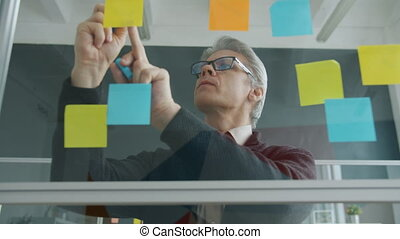 Mature businessman is writing oncolorful sticky notes on office glass wall busy with business planning making mind map. Businesspeople and creativity concept.