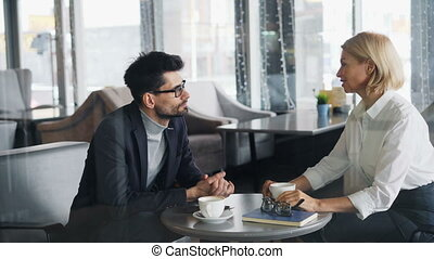 Mature businesspeople in formalwear talking in cafe during...