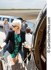Mature Businesswoman Boarding Private Jet - Mature...