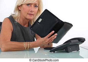 mature businesswoman looking at her agenda