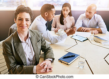 Mature businesswoman looking at the camera during business meeting