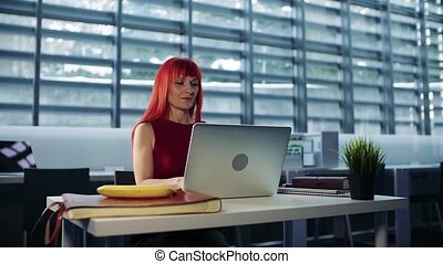 Mature businesswoman sitting at desk in office, using...