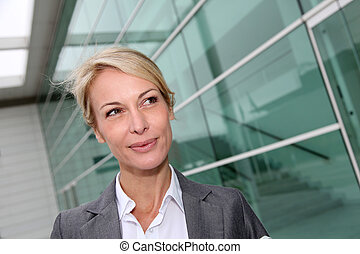 Mature businesswoman standing in front of modern building