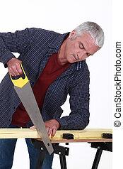 mature carpenter using saw