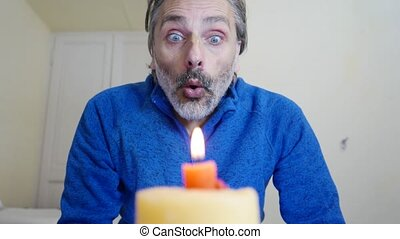 Mature caucasian man blowing candle at home - out of focus...