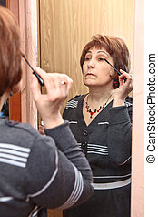 Mature Caucasian woman applying make-up against mirror in domestic room