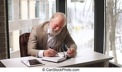 Mature classy old man working in his home office.