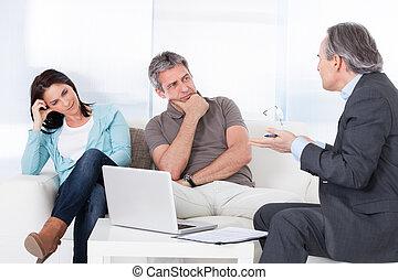 Mature Consultant Explaining To Couple