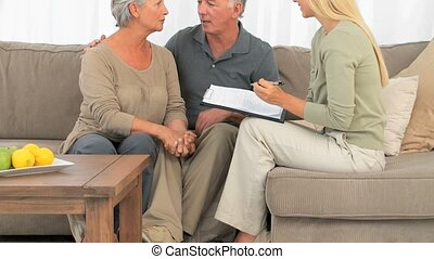 Mature couple answering to a commercial woman at home