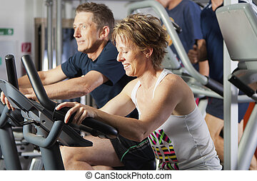 Mature couple at fitness centre - Mature couple working out...