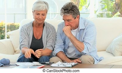 Mature couple calculating their bills in the living room
