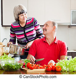 mature couple cooking  in kitchen at home