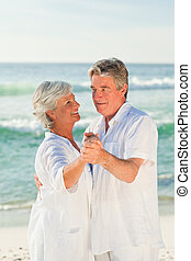 Mature couple dancing on the beach