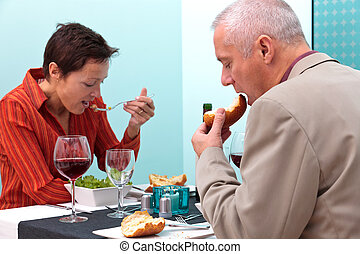 Mature couple eating food in a restaurant