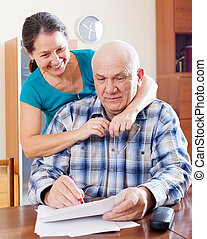 mature couple fills in  documents