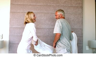 Mature couple having a pillow fight