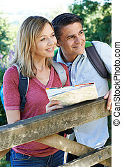 Mature Couple Hiking In Countryside With Map