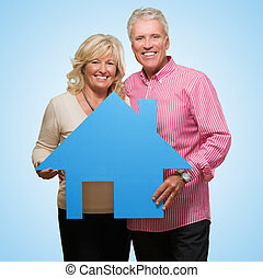 Mature Couple Holding Model Of A House