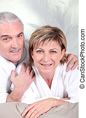 Mature couple in bathrobe laid on a bed