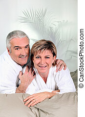 Mature couple in bathrobes on a bed