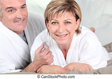 Mature couple in bed with bathrobe