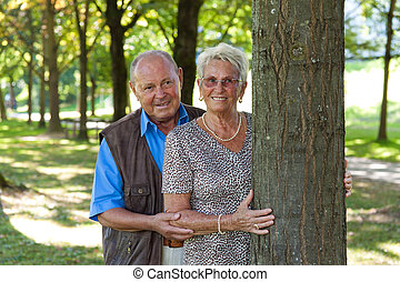 Mature couple in love senior citizens is available at a tree.