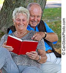 Mature couple in love seniors read a book.
