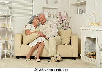 mature couple in modern room, posing on sofa