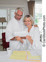 Mature couple looking at a document at home
